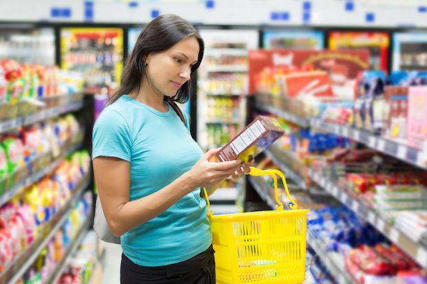 donna al supermercato guarda l'etichetta di un prodotto