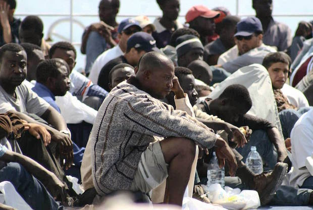 Asylum seekers, part of the some 350 Africans who arrived 14 and 15 June 2003 on the island of Lampedusa wait to betransferred by police to Agrigento, Lampedusa main city,16 June 2003. The xenophobic leader of Italy's Northern League and cabinet minister Umberto bossi suggested today using cannons to combat the growing problem of immigration, as the government prepares to implement more restrictive asylum policies. AFP PHOTO/ANSA/FRANCO LANNINO